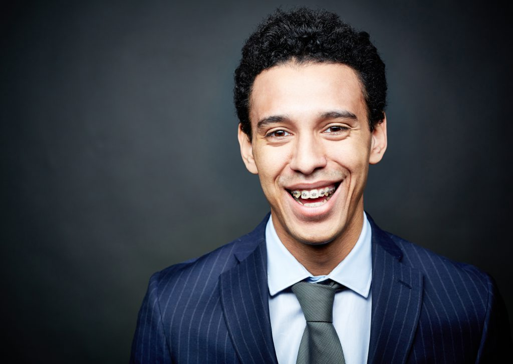young man in a suit smiling with braces