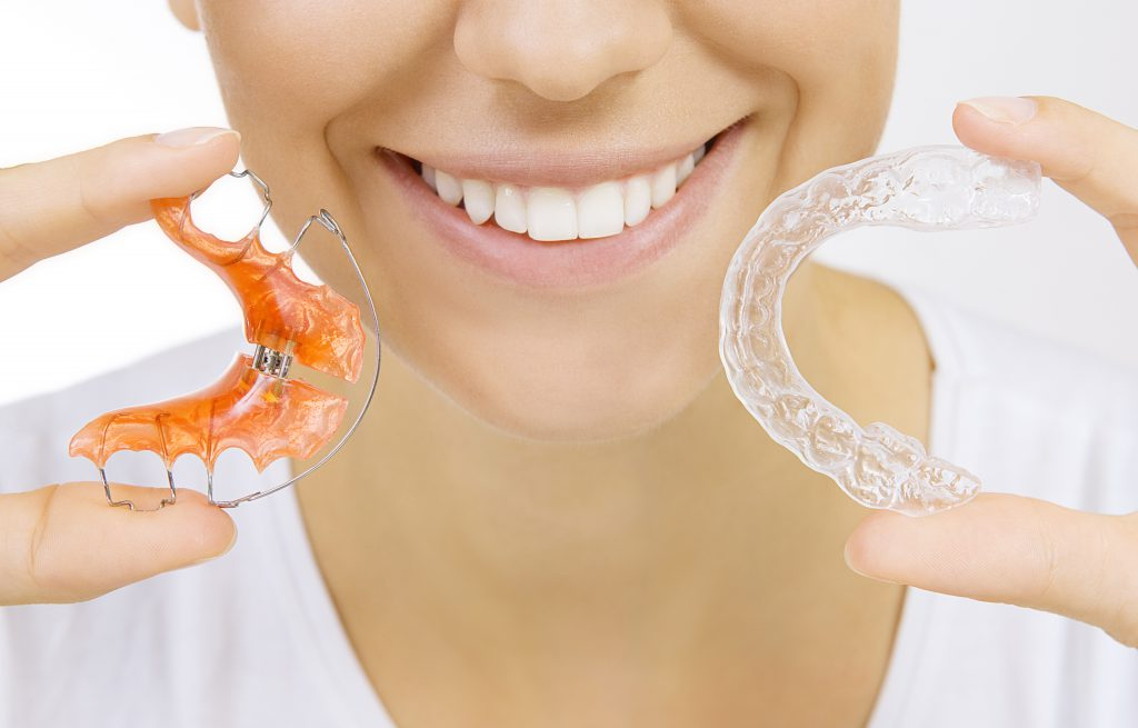 Smiling girl holding retainer for teeth (dental braces) and individual tooth tray