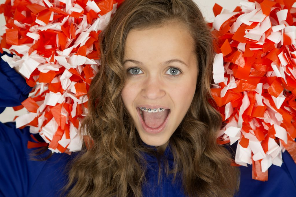 Excited cute teenage cheerleader smiling and wearing braces