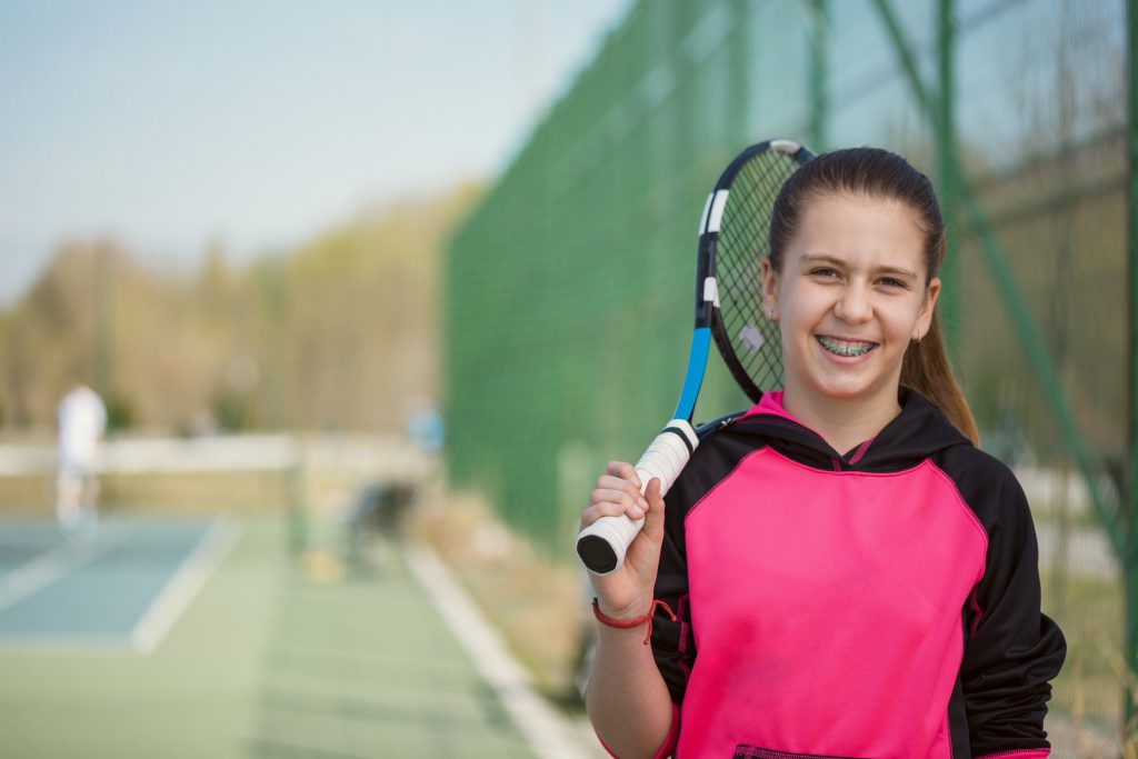 Young Girl With Braces Smiling and Holding A Tennis Racket