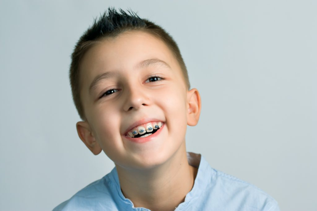 laughing boy with braces in front of light blue background
