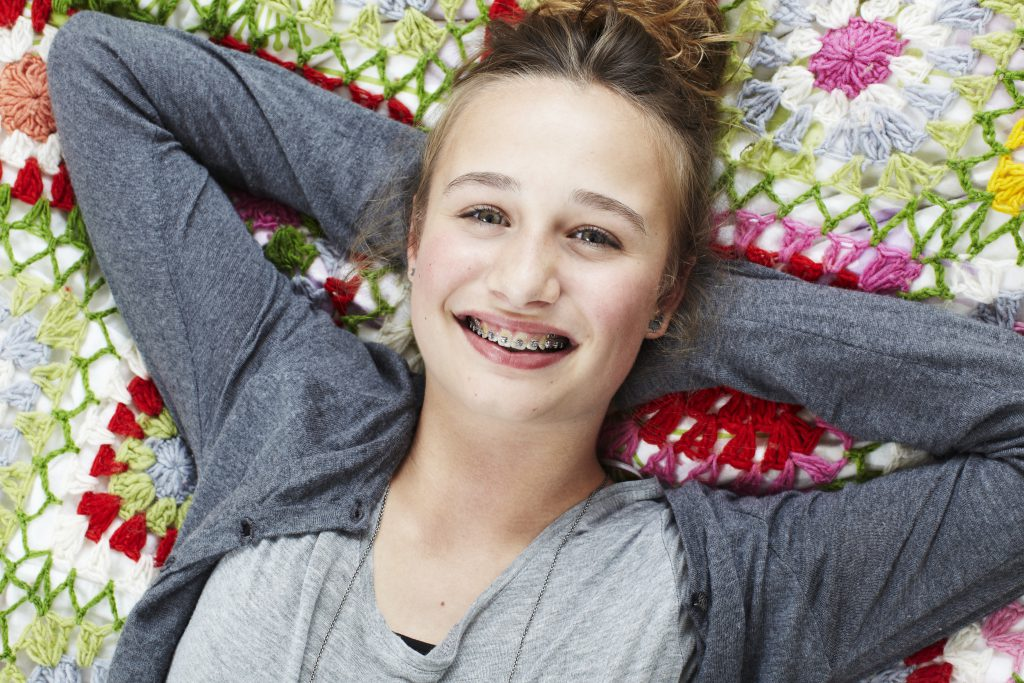 Smiling teenage girl with braces lying on a blanket